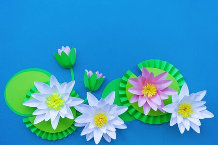Waterlily flower made of paper. Blue background. Origami hobby. Gentle petal. Marsh with frogs tradition.