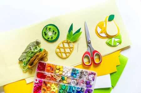 Felt stitched fruit. Material and tools for creativity on a white background. Sewing toys for a child. Bright color Archivio Fotografico