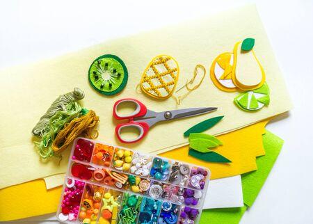 Frutta cucita in feltro. Materiale e strumenti per la creatività su sfondo bianco. Giocattoli da cucire per un bambino. Colore brillante Archivio Fotografico