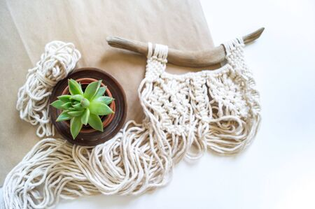 Macrame weaving from natural cotton threads. Home decor vintage boho style. Decorative panel on a wooden branch. Natural