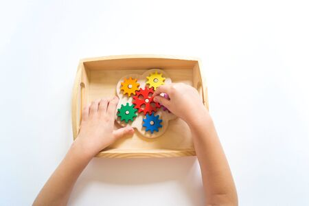 Montessori gear material. The color of the rainbow. Hands of a child are playing. School for child development. Imagens