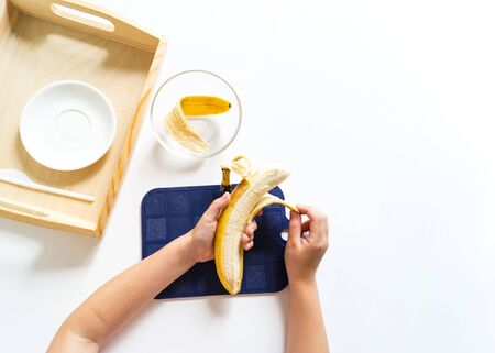 Montessori cooking material in the kitchen. Child's hand peels and cuts a banana. Breakfast.