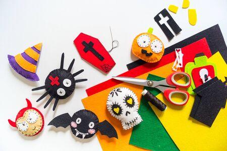 Giocattolo in feltro per decorazioni di halloween da officina. Scheletro del cranio del diavolo del gatto nero del pipistrello del ragno su una priorità bassa bianca. Materiale per la creatività e il cucito. Festa di Halloween.