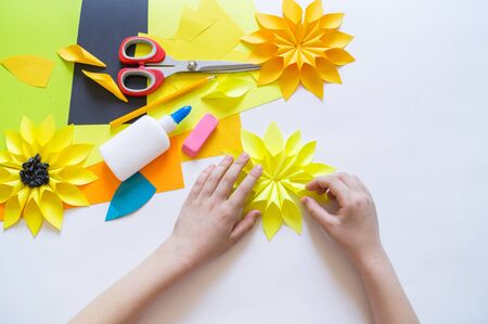 The hands of the child makes an odd flower paper out of sunflower. Yellow plant summer. The creative process. Kindergarten and school development. Master Class.