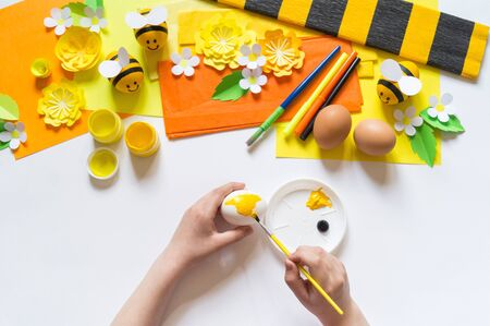 Child hands girl paints an Easter egg. Egg a yellow bee. White background. Material for creativity, paint and paper. Mastery lesson kindergarten.