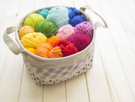 Yarn for knitting rainbow. Wood background. Favorite hobby. Thread in basket