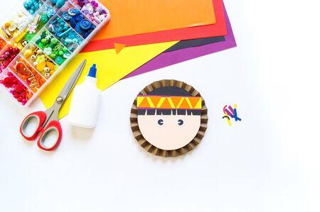 Craft paper Indian man. Craftsmanship for children. Red-skinned man toy