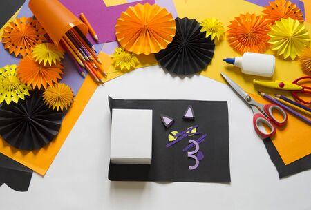 Halloween holiday black cat made of paper. Children's creativity. Hobby craft material Foto de archivo