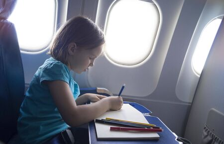 A child draws with pencils while sitting in an airplane. Games while traveling.