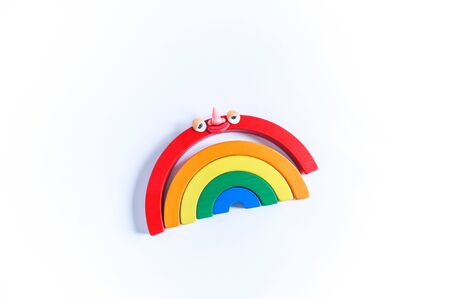 Toy rainbow with eyes and mouth of plasticine. Conceptual photo. White background.