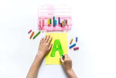 Children's hands write the letter A chalk. White background. Write ABC. Office back to school