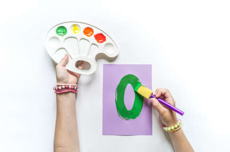 Children's hands write the letter O paint gouache. White background. Write ABC. Office back to school