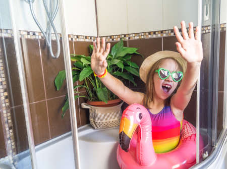 Defocus Little girl sits in the bathroom, imagines that she is resting on the sea. Self isolation due to virus. Stay home and play. Inflatable swimming circle flamingo.