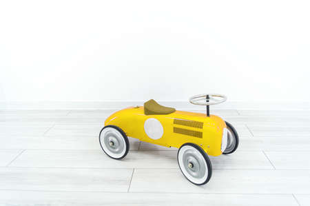 Toy yellow retro car. The child plays with transport. White background.