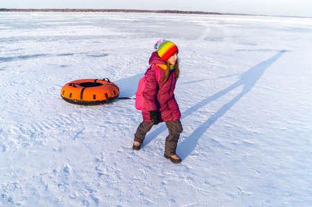 happy child rolls tubing inflatable sledges Merry winter holidays. Family ski resort