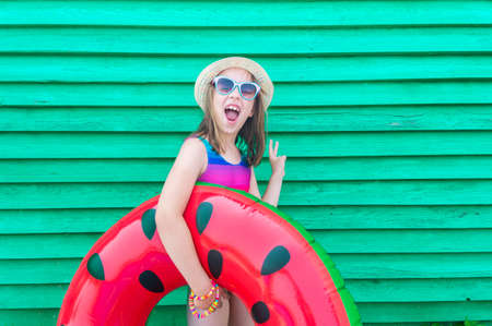 Girl with an inflatable watermelon. Wooden green background. Active holidays with family on the beach pool. Emotional kid