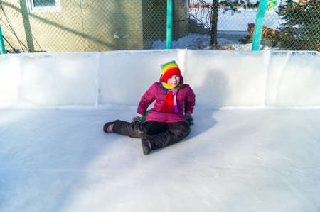 Child rolls down an ice slide. Merry winter sport family. Bright clothes rainbow hat.