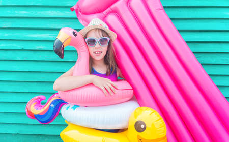 Girl air mattress. Child in hat and glasses on a wooden background. Relax on the beach pool Emotional kid