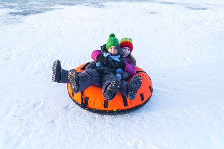 happy child riding on the tubing. inflatable sledges Happy winter holidays. Family ski resort. Boy and girl Archivio Fotografico