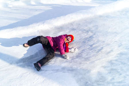 The girl is wallowing in the snow. Fell down the hill. Merry winter sport family. Bright clothes rainbow hat.