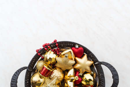 Christmas decorations in a round wicker basket. Gold red star and ball