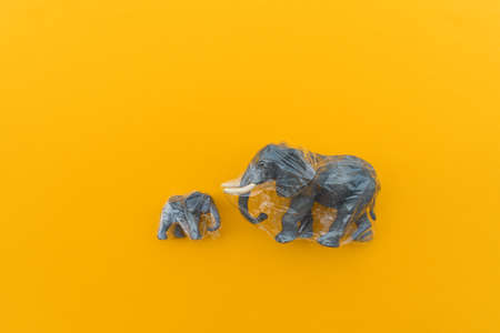 Elephant is entangled in a plastic bag. Plastic animal concept. Yellow background. Environmental pollution problem.