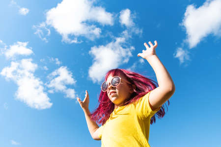 Attractive young girl with pink hair is Jumping. Sky background with clouds. Party and fun concept. Kid hair magnificent Stock fotó