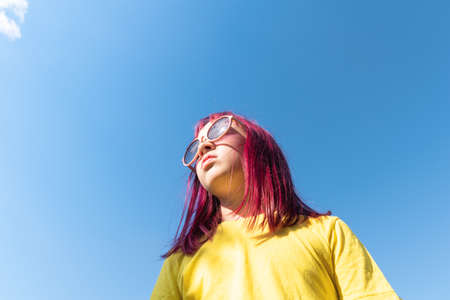 Attractive young girl with pink hair is dancing. Sky background with clouds. Party and fun concept. Kid hair magnificent Stock fotó
