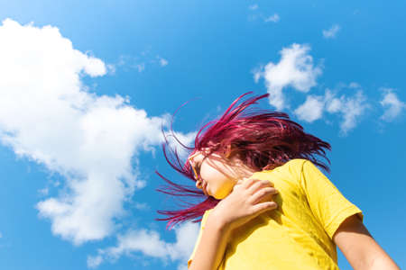 Attractive young girl with pink hair is dancing. Sky background with clouds. Party and fun concept. Kid hair magnificent Reklamní fotografie