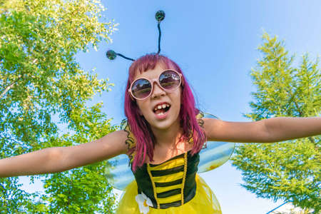 Girl in a bee costume with pink hair outdoors. Looks into the camera Child pretends fly. Blue sky background Copy space Reklamní fotografie