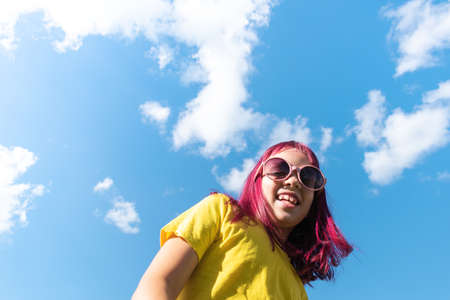 Attractive young girl with pink hair is dancing. Sky background with clouds. Party and fun concept. Kid hair magnificent Reklamní fotografie - 161459683