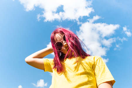 Attractive young girl with pink hair is dancing. Sky background with clouds. Party and fun concept. Kid hair magnificent Reklamní fotografie - 161459684
