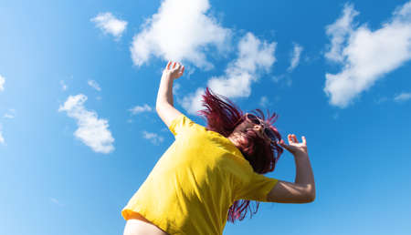 Attractive young girl with pink hair is Jumping. Sky background with clouds. Party and fun concept. Kid hair magnificent Reklamní fotografie