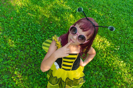 Girl in a bee costume with pink hair outdoors. Child is sitting on the green grass. Carnival in costumes.