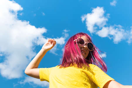 Attractive young girl with pink hair is dancing. Sky background with clouds. Party and fun concept. Kid hair magnificent 版權商用圖片