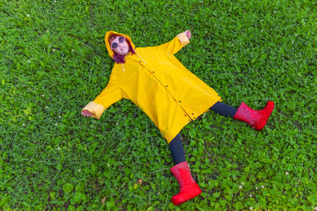 Girl in a yellow raincoat. Outdoors walk. Kid lies on the green grass. Hipster child teenager in pink glasses. Summer heat. Reklamní fotografie - 161459529