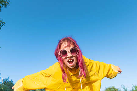 Girl in a yellow raincoat. Summer walk. Blue sky background. Hipster teenager having fun and looking at the camera 版權商用圖片