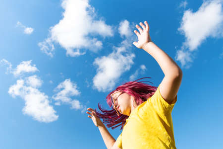 Attractive young girl with pink hair is Jumping. Sky background with clouds. Party and fun concept. Kid hair magnificent Reklamní fotografie - 163395160