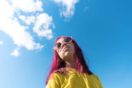 Attractive young girl with pink hair is dancing. Sky background with clouds. Party and fun concept. Kid hair magnificent Reklamní fotografie - 163395164