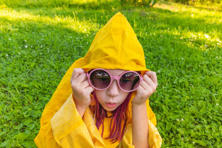 Girl in a yellow raincoat. Outdoors walk. Kid lies on the green grass. Hipster child teenager in pink glasses. Summer heat.