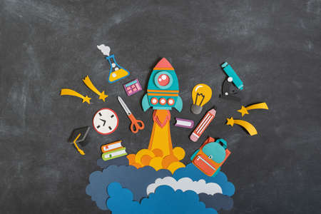 Rocket takes off paper craft. Back to school. Copy space. Black background school board. Education concept
