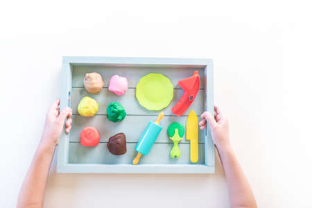 Montessori material is plasticine. Chef education game. Children's hands on a wooden tray. White background