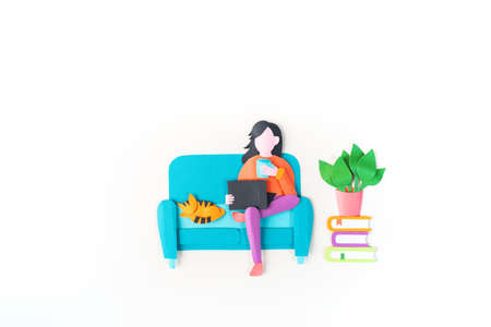 Woman sitting a blue couch working on a laptop. Paper craft creativity Online education learning at home White background Reklamní fotografie