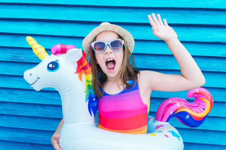 Girl circle unicorn. Baby in hat and glasses on a wooden background. Active holidays with family on the beach pool. Emotional kid 版權商用圖片