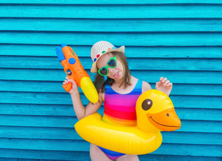 Girl with an inflatable duck. Baby in hat and glasses on a wooden background. Active holidays with family on the beach pool. Emotional kid