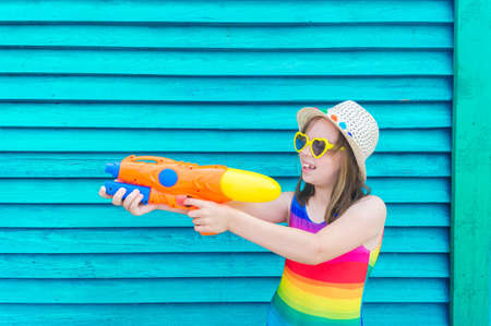 Girl with a water gun. Baby in hat and glasses on a wooden background. Active holidays with family on the beach pool. Emotional kid