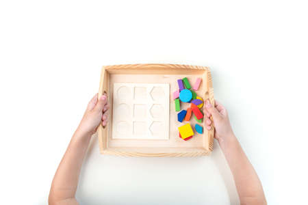 Montessori material. Hand of a child. White background. Toddler education. Study of mathematic and letter. School and kindergarten.