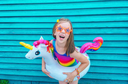 Girl circle unicorn. Baby in hat and glasses on a wooden background. Active holidays with family on the beach pool. Emotional kid Reklamní fotografie