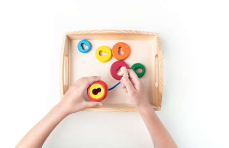 Montessori material. Hand of a child. White background. Toddler education. Study of mathematic and letter. School and kindergarten. Reklamní fotografie - 162991445