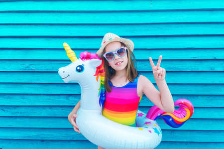 Girl circle unicorn. Baby in hat and glasses on a wooden background. Active holidays with family on the beach pool. Emotional kid Reklamní fotografie - 163395843